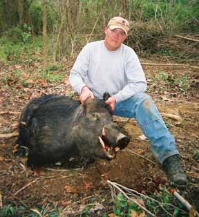 My husband Mike with a live wild boar that our pit bull Semi-Sweet caught.